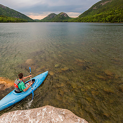 A man kayaking on Jordan Pond in Maine's Acadia National Park.