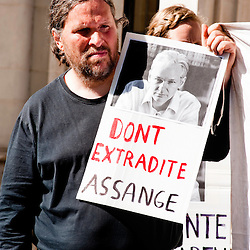 "LONDON, UK - 30th May 2012: a protester holds a sign reading ""Don't extradite Assange outside The Supreme Court in London, minutes after Assange's loss of his extradition appeal."