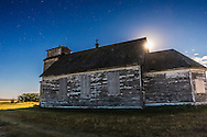 The Moon appears from behind the old St. Anthony's Church south of Bow Island, Alberta in a moonlit nightscape. The Church was built in 1911 by English and Russian-German immigrants. This is a single frame from a 300-frame time-lapse sequence.