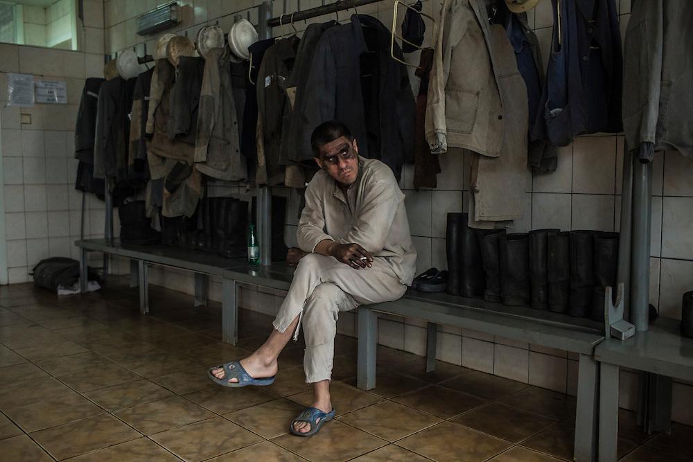 A miner smokes a cigarette after going underground at the Shcheglovskaya Coal Mine on Friday, March 25, 2016 in Makiivka, Ukraine.