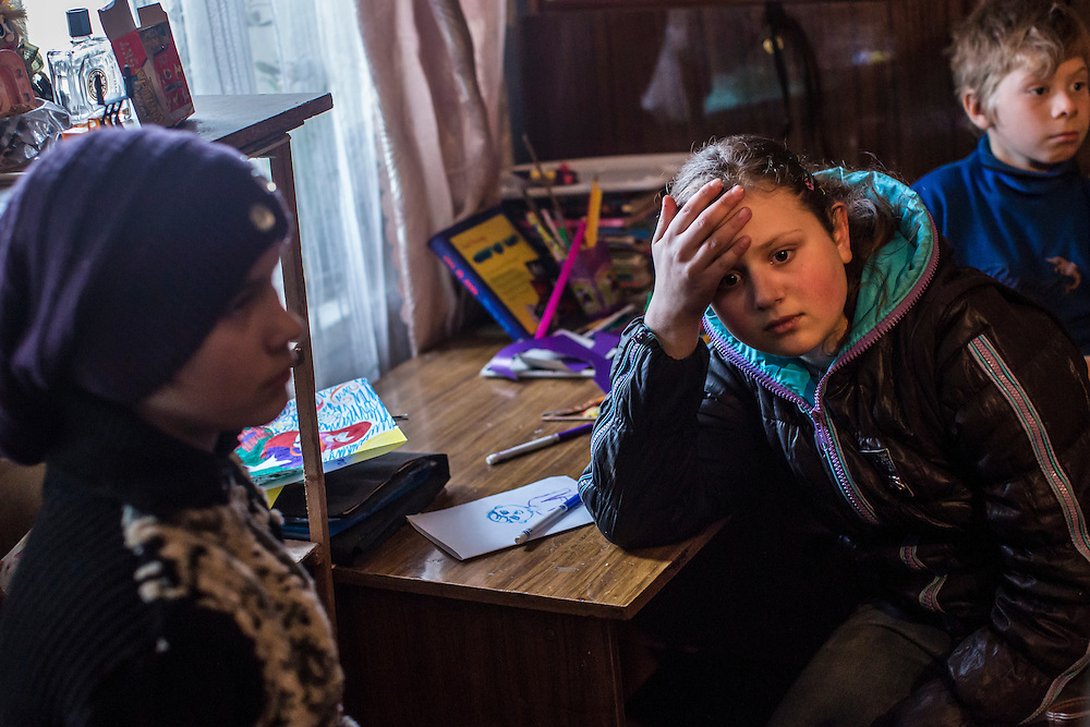 Diana, age 11, Elena, age 13, and Nikolai, age 9, listen as a military chaplain tries to convince their families to allow the children to move away from the dangers of life on the Ukrainian-controlled front line on Saturday, February 13, 2016 in Zaitseve, Ukraine. The town itself is half controlled by Ukrainian forces and half by pro-Russian rebels, leading to regular fighting.