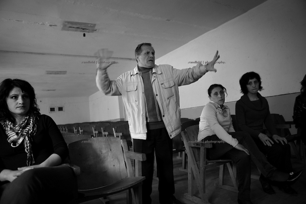"""Actors of Shushi theater during a rehearsal. Director Leonid gestures (c.). This image is part of the photoproject """"The Twentieth Spring"""", a portrait of caucasian town Shushi 20 years after its so called """"Liberation"""" by armenian fighters. In its more than two centuries old history Shushi was ruled by different powers like armeniens, persians, russian or aseris. In 1991 a fierce battle for Karabakhs independence from Azerbaijan began. During the breakdown of Sowjet Union armenians didn´t want to stay within the Republic of Azerbaijan anymore. 1992 armenians manage to takeover """"ancient armenian Shushi"""" and pushed out remained aseris forces which had operate a rocket base there. Since then Shushi became an """"armenian town"""" again. Today, 20 yeras after statement of Karabakhs independence Shushi tries to find it´s opportunities for it´s future. The less populated town is still affected by devastation and ruins by it´s violent history. Life is mostly a daily struggle for the inhabitants to get expenses covered, caused by a lack of jobs and almost no perspective for a sustainable economic development. Shushi depends on donations by diaspora armenians. On the other hand those donations have made it possible to rebuild a cultural centre, recover new asphalt roads and other infrastructure. 20 years after Shushis fall into armenian hands Babies get born and people won´t never be under aseris rule again. The bloody early 1990´s civil war has moved into the trenches of the frontline 20 kilometer away from Shushi where it stuck since 1994. The karabakh conflict is still not solved and could turn to an open war every day. Nonetheless life goes on on the south caucasian rocky tip above mountainious region of Karabakh where Shushi enthrones ever since centuries."""