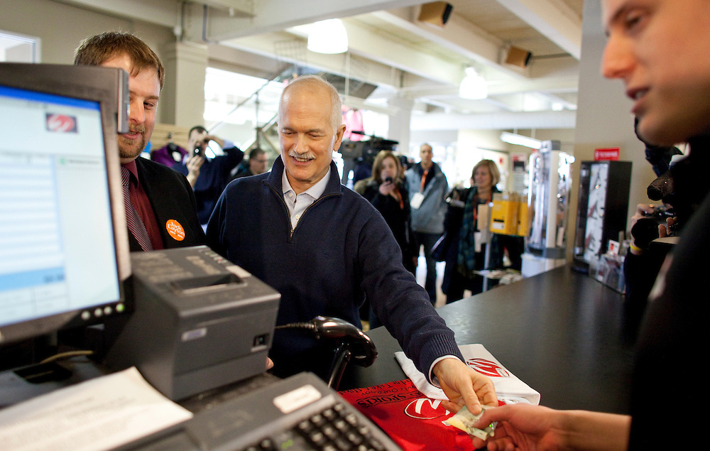 NDP leader Jack Layton purchases some t-shirts with cash during a campaign stop at Webco Sports store in Kitchener, Ontario, March 29, 2011. Earlier in the day Layton announced his plan to limit credit card fees for consumers and small businesses. Canadians will be heading to the polls May 2.<br /> AFP/GEOFF ROBINS/STR