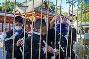 Schoolboys tie prayer notes at Shinto shrine.