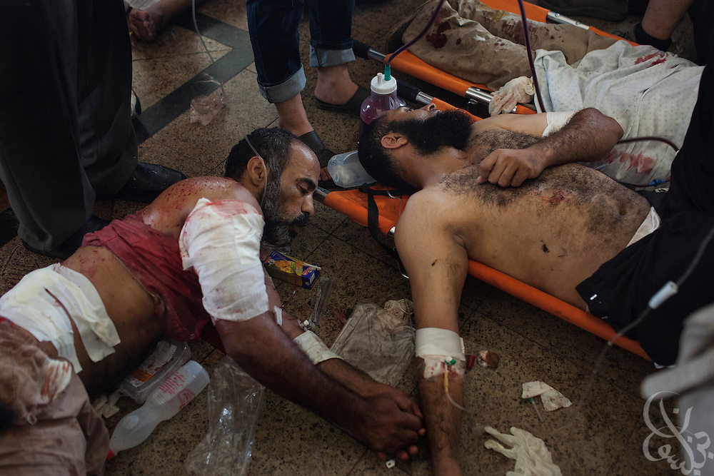 The wounded lie next to one another on stretchers inside a packed field hospital inside the Rabaah al-Adawiya protest camp in Nasr City during the August 14, 2013 Ministry of Interior/Police operation to clear the protest by force. The assault, which began at 7am with police moving in to seal the surrounding streets included tear gas and live fire, and there are reports of large numbers of killed and wounded protesters.