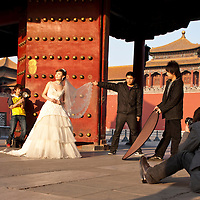 China, Beijing, Young woman poses in white gown for elaborate wedding portraits at entrance gate to Forbidden City on spring evening
