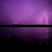 """Rain falling on the James River with lightning storm over historic Jamestown Island. Site of the first permanent English settlement in the New World, established in 1607, Virginia. This view is from the Colonial Parkway in the Colonial National Historical Park (U.S. National Park Service,) in Virginia's """"Historic Triangle"""" (Jamestown-Williamsburg-Yorktown.)"""
