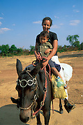 Mother on  mule back with son, Brazilian Highlands, Goias, Brazil