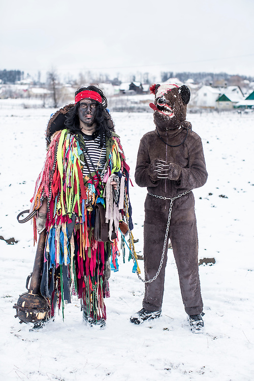 Ivan Usaki, 14, left, Vasyl Mytryk, 16, in the costumes of a gypsy and a bear respectively, pose for a portrait during celebrations of the Malanka Festival on Thursday, January 14, 2016 in Krasnoilsk, Ukraine. The annual celebrations, which consist of costumed villagers going in a group from house to house singing, playing music, and performing skits, began the previous sundown, went all night, and will last until evening.