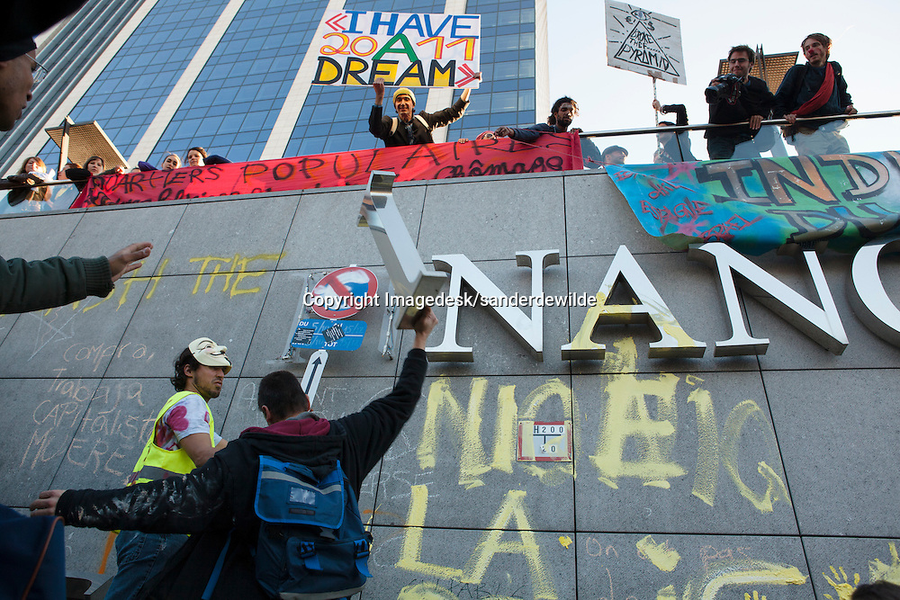 Indignados protests against the financial crisis and the power of banks and kapitalism. Occupy activists painting on the walls of the Federal Finance Tower. Brussels Belgium 15 october 2011