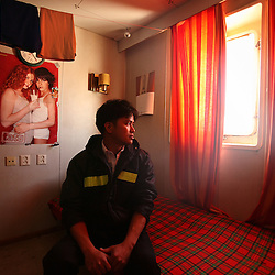 Renante Benamir, 29, of Laguna, Philippines, takes a rest in his room at lunch time in Piraeus, Greece on Feb. 20, 2008. Benamir had just began his 7-month. The Alfa K, a Mediterranean based bulk carrier with a Panamanian flag, was undergoing repairs at the port of Piraeus. Inspectors impose ITF-standard treaties on ship-owners to guarantee minimal standard working conditions for seafarers. They are on call 24 hours a day to address concerns from workers coming to port on the international ships.
