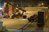 A container crane plucks an inbound container off a truck chassis in preparation of its getting loaded onto the outbound rail cars on the right. This action is taking place at the small intermodal yard adjacent to Canadian Pacific's giant Bensenville, IL freight classification yard.