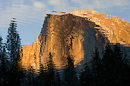 Ripples in the Merced River break up a sunset reflection of Half Dome in Yosemite National Park