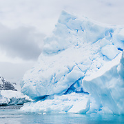A blue iceberg juts from the Southern Ocean offshore from Graham Land, the north part of the Antarctic Peninsula, Antarctica.