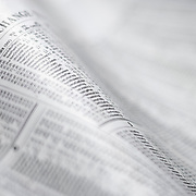 Abstract of newspaper stock exchange listing with shallow focus and curved paper.