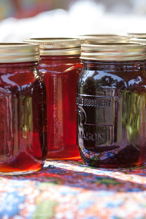 Mason jars of Maple Syrup in the sun on a table at a farmers market
