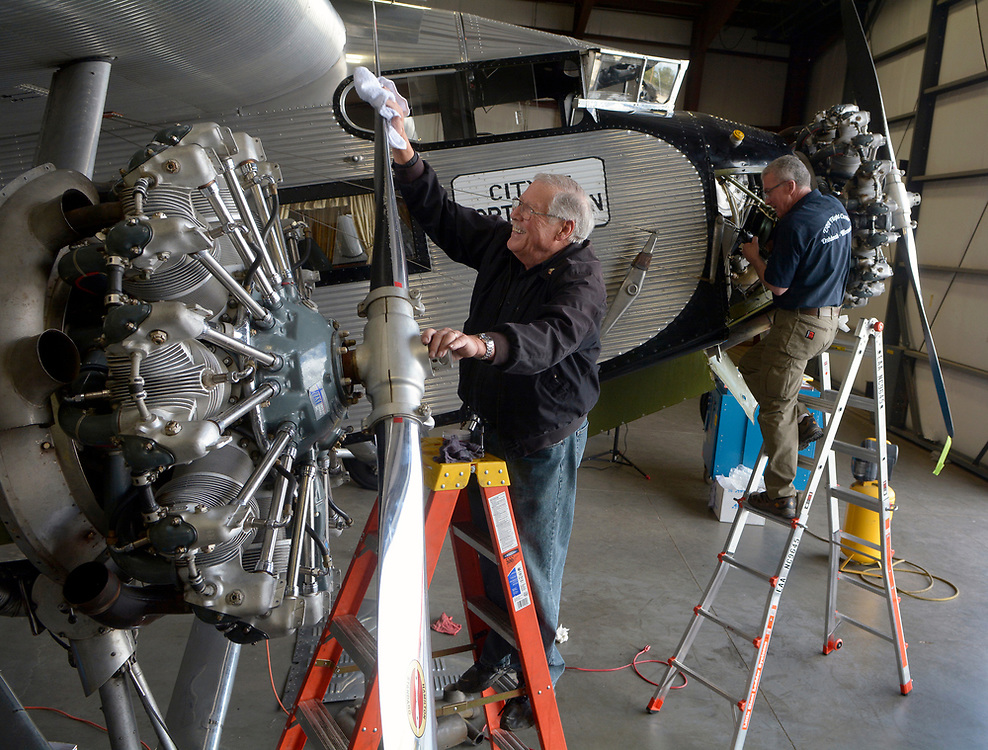 gbs040317i/ASEC -- Paul Cross of Corrales polishes a propeller as Tim Brooks of Oskosh, Wisconsin works on the magnetos of the Ford Tri-Motor operated by the Experimental Aircraft Association at Double Eagle II Airport on Monday, April 3, 2017. The plane is undergoing a 100-hour inspection. Rides on the 1928 Transcontinental Air Transport passenger airplane will given April 6-9 at Double Eagle II Airport. The plane is hosted by Albuquerque's EAA Chapter 179. (Greg Sorber/Albuquerque Journal)