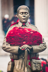 Trafalgar Square, London, Friday 7 November. The Royal British Legion unveiled the Every Man Remembered sculpture in Trafalgar Square, a collaborative piece with the artist Mark Humphrey. The brass sculpture, loosely based on the Unknown Solider, stands on a plinth of limestone sourced from the Somme and is encased in a Perspex obelisk, surrounded by poppies which float up around the figure every five minutes. PICTURED: Cradled in his arms, a precious burden of poppies.