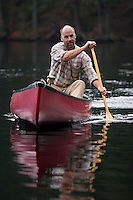 John Stowell paddles a canoe across a small pond in the Adirondacks, New York.