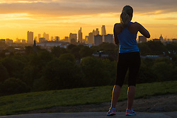Primrose Hill, London, September 27th 2016. A runner takes a picture of the London skyline on Primrose Hill as dawn breaks over the capital. &copy;Paul Davey<br /> FOR LICENCING CONTACT: Paul Davey +44 (0) 7966 016 296 paul@pauldaveycreative.co.uk