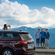 A foreign tourist family taking a photo in front of the view from Hurricane Ridge looking south towards the main peaks and glaciers. Olympic National Park.