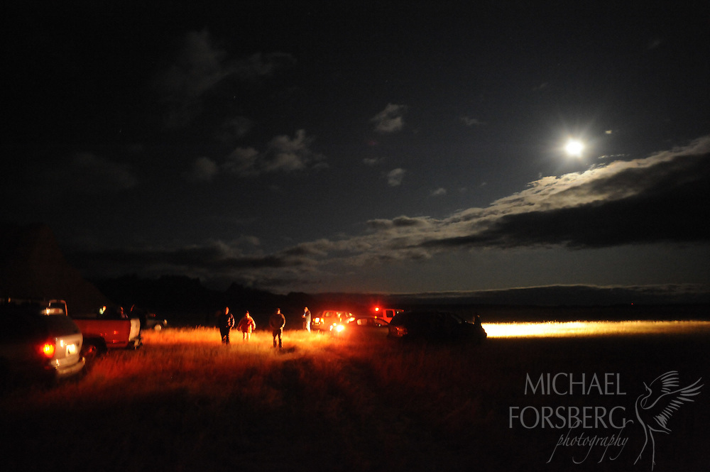 Northern Great Plains region:  Badlands, Conata  Basin, South Dakota..USFS Moon Walk participants come back from a moonlit hike and gather at their vehicles at the Conata Basin Ranch (TNC), next to the Sage Creek Wilderness Area.