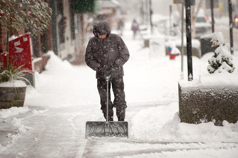 Rick Heisler shovels snow of the sidewalk along Cleveland Avenue. Squamish BC, Canada.