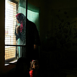 A family from Fallujah rests inside a home, Baghdad, Iraq, April 12, 2005. They escaped by crawling on their knees to an ambulance and then traveling to Baghdad in a refrigerated meat truck. Hospital officials in Fallujah report more than 600 killed and more than 1200 wounded, most of which they say were women, children and elderly.