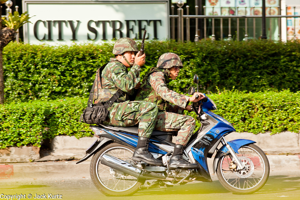 14 MAY 2010 - BANGKOK, THAILAND: Thai soldiers try to evade rockets and stones from Red Shirt protesters at the intersection of Rama IV and Witthayu Roads in Bangkok Friday morning. Tensions among Red Shirt protesters demanding the dissolution of the current Thai government rose overnight after Seh Daeng, the Red Shirt's unofficial military leader was shot in the head by a sniper. Gangs of Red Shirts have taken over military checkpoints on Rama IV and are firing small rockets at military helicopters and army patrols in the area. Troops have responded by firing towards posters.  PHOTO BY JACK KURTZ