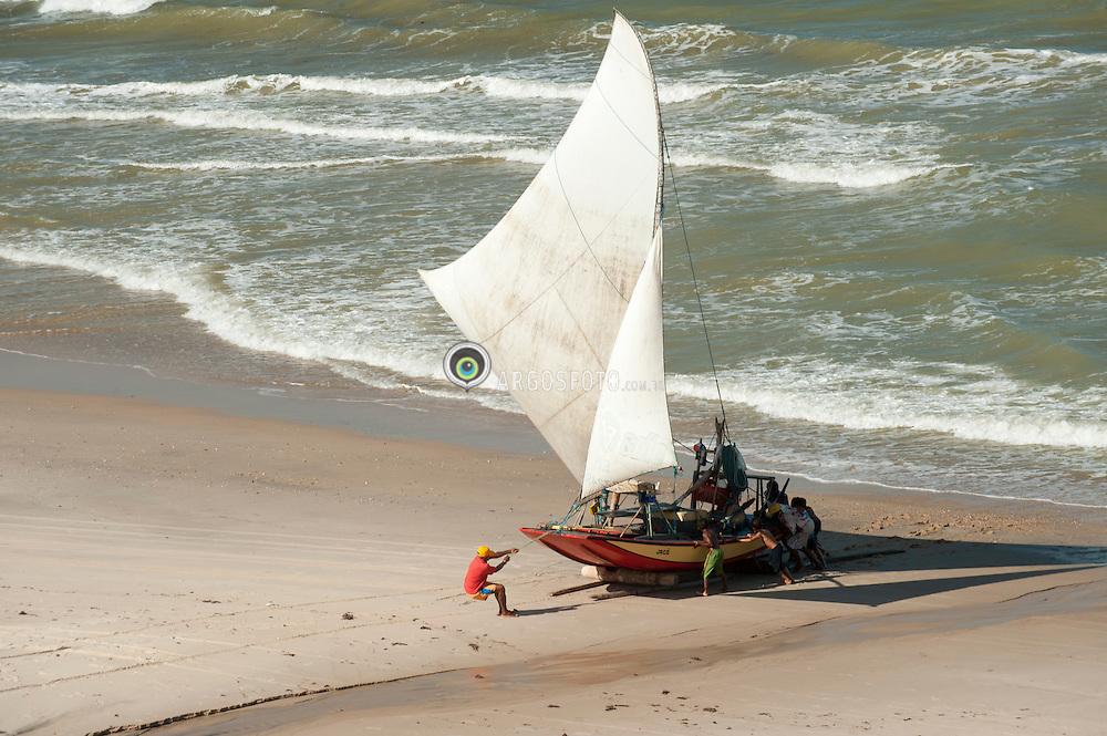Pescadores puxam a jangada do mar para praia em  Quixaba no estado brasileiro do Ceara./Fishermen pull the raft to the beach on the sea beach Quixaba the Brazilian state of Ceara.
