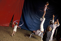 "Family of acrobats practice/train young children.  Bentley Bros. circus, one of the few remaining ""mud show"" circus performing under a canvas big top."