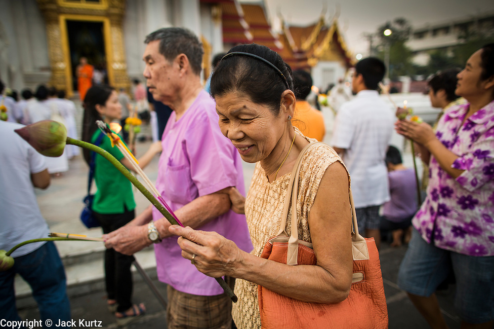 """25 FEBRUARY 2013 - BANGKOK, THAILAND:  People participate in a procession around Wat Benchamabophit Dusitvanaram (popularly known as either Wat Bencha or the Marble Temple) on Makha Bucha Day. Thais visit temples throughout the Kingdom on Makha Bucha Day to make merit and participate in candle light processions around the temples. Makha Bucha is a Buddhist holiday celebrated in Myanmar (Burma), Thailand, Cambodia and Laos on the full moon day of the third lunar month (February 25 in 2013). The third lunar month is known in Thai is Makha. Bucha is a Thai word meaning """"to venerate"""" or """"to honor"""". Makha Bucha Day is for the veneration of Buddha and his teachings on the full moon day of the third lunar month. Makha Bucha Day marks the day that 1,250 Arahata spontaneously came to see the Buddha. The Buddha in turn laid down the principles his teachings. In Thailand, this teaching has been dubbed the 'Heart of Buddhism'.     PHOTO BY JACK KURTZ"""