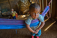 Child in the La Concordia area of Nicaragua leans on a hammock, watching his mother do housework.