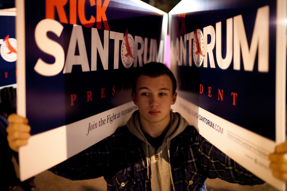 Kyle Mercer of Merrimack, New Hampshire, holds signs for Republican presidential candidate Rick Santorum outside the site of the WMUR/ABC News Debate at Saint Anselm College on Saturday, January 7, 2012 in Manchester, NH. Brendan Hoffman for the New York Times