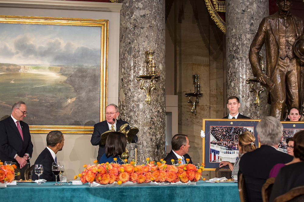 Sen. Lamar Alexander (R-TN) presents President Barack Obama with the gift of a framed photograph of his Inauguration at the Inaugural Luncheon in Statuary Hall at the U.S. Capitol on Monday, January 21, 2013 in Washington, DC.