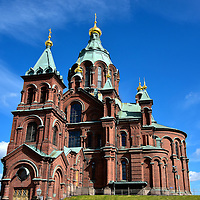 Uspenski Cathedral in Helsinki, Finland<br /> High on a hill in the Katajanokka neighborhood of Helsinki is the stunning Uspenski Cathedral. This Byzantine-Russian church was built in 1868 using bricks from the Bomarsund Fortress after it was destroyed during the Crimean War. The church&rsquo;s best architectural feature is a dozen gilded onion domes representing the Apostles. They surround the larger central dome symbolizing Christ.  Uspenskin Katedraali was dedicated to the Virgin Mary.  It is Western Europe&rsquo;s largest Orthodox church and it is the seat of the Archdiocese of Helsinki.