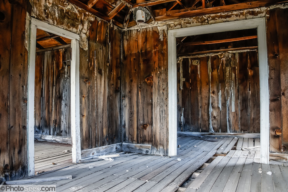 """Dilapidated doors in a ramshackle building at Bodie, California's official state gold rush ghost town. Bodie State Historic Park lies in the Bodie Hills east of the Sierra Nevada mountain range in Mono County, near Bridgeport, California, USA. After W. S. Bodey's original gold discovery in 1859, profitable gold ore discoveries in 1876 and 1878 transformed """"Bodie"""" from an isolated mining camp to a Wild West boomtown. By 1879, Bodie had a population of 5000-7000 people with 2000 buildings. At its peak, 65 saloons lined Main Street, which was a mile long. Bodie declined rapidly 1912-1917 and the last mine closed in 1942. Bodie became a National Historic Landmark in 1961 and Bodie State Historic Park in 1962."""