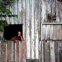 South America, Brazil, Amazon.  An Amazon resident watches from his window in contemplation.
