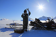 Glaciologist Jack Kohler of the Norwegian Polar Institute sets up GPS beacon to measure ice flow atop Kongsvegen glacier 750 meters (2460 feet) above sea level at Kongsfjorden; Svalbard, Norway.