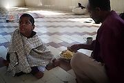 Assisting a young mentally ill boy to eat food at the Edhi Foundation Home for Men and Boys on the outskirts of Karachi. The facility currently holds some 1132 men and 300 boys with a staff of 40 including one doctor. Te shelter acts as a 'catch all' safety net giving those who are mentally or physically disabled as well as those who have no where else to go a refuge in a the absence of any state help. most at the facility have been abandoned by their families, and have nothing in the way of personal possessions, the clothes they wear are mostly donated. there are no education/voactional training facilities on site for adults and medical support is basic at best...The youngest, a mentally disable boy is 8 years old whilst the oldest, an 84 years old homeless person. According to Dr Kamal the resident doctor, there are about 80-100 admissions in a week to the senior citizens hall while between approximately 16 people die every month, mostly because of old age. ..The mentally disabled patients receive occasional consultant visits and whilst they are administered prescribed medicines to keep them manageable, no measures are taken to improve their condition or help them become independent in their daily routine...The Edhi facility is able to meet merely their survival needs of the men and boys. Some patients are visited by relatives, very few leave the facility unless there is a guarantee of care from a relative. meals are basic consisting of traditional biryani type rice dish and there is little in the way of running water and electricity. At the time of visit water bowsers were being delivered to the the facility to cater for water consumption. patients sleep some 30 to a room some as may as 80 depending on the mental and physical abilities of the patients....In a country of some 160 million people, affordable medicines and diagnostic tests are beyond the reach of most people in Pakistan. The country suffers from shortage of doctors and government funded healthcare fa