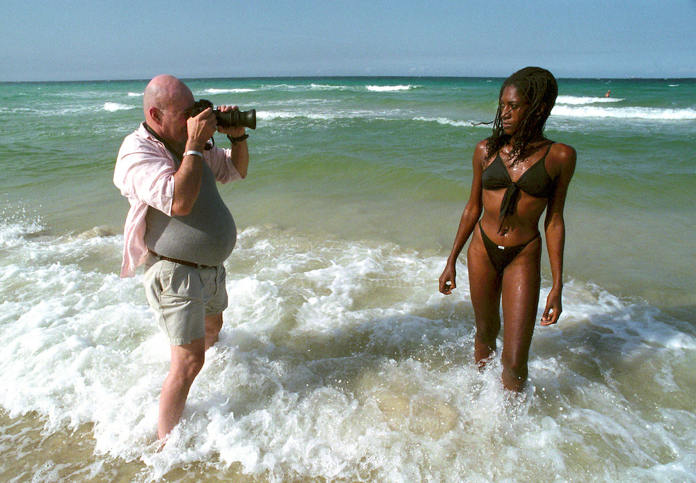 An American takes a photo of Laritza, a young Cuban woman hired as a model for a photography course at Playa Santa Maria, just outside Havana, Cuba.