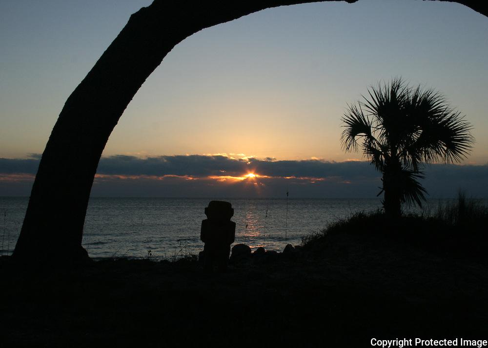 A tiki god stands guard at sunrise on a tropical beach.