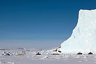 Canadian Rangers ride snowmobiles on icepack next to an adrift iceberg off Gascoyne Inlet (Devon Island, Nunavut) during Nunalivut 2012 sovereignty exercise by Canadian Forces in arctic Canada.