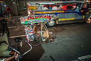 Homeless man in a wheelchair navigates heavy traffic on Mabini Street in the Malate District where many homeless people can be founded living and sleeping on the sidewalks.  Malate, Manila, Philippines.<br /> <br /> President-elect Rodrigo Duterte inherits a country where the rich live a parallel in gated communities, while the poor and middle income struggle in a crowded, environmentally degraded environment but rarely to those two worlds meet.