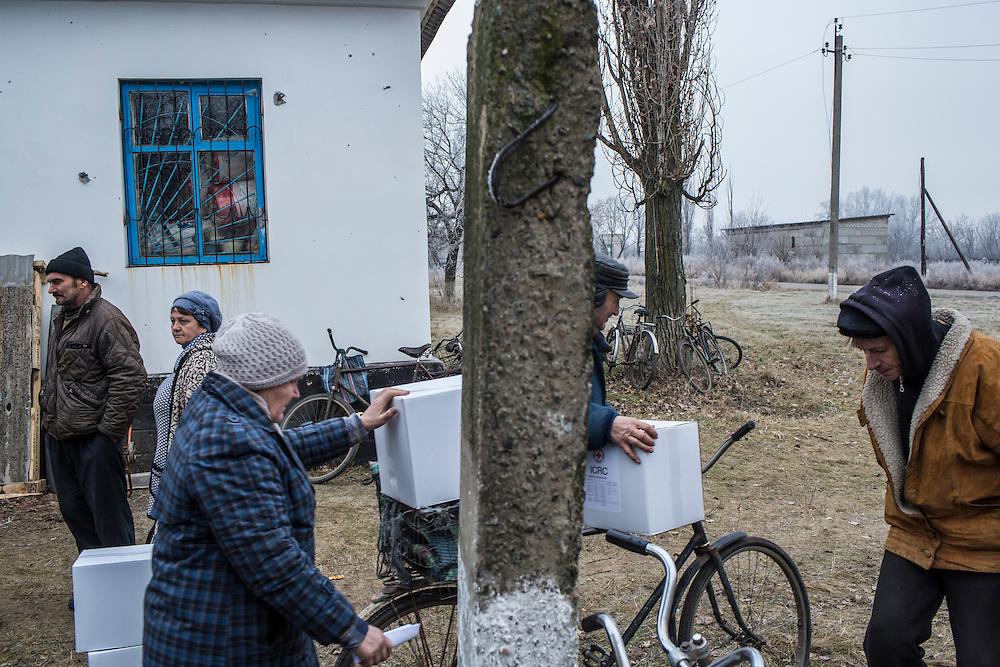 Local residents take boxes of food and supplies delivered by the ICRC on Friday, December 11, 2015 in Troitske, Ukraine.