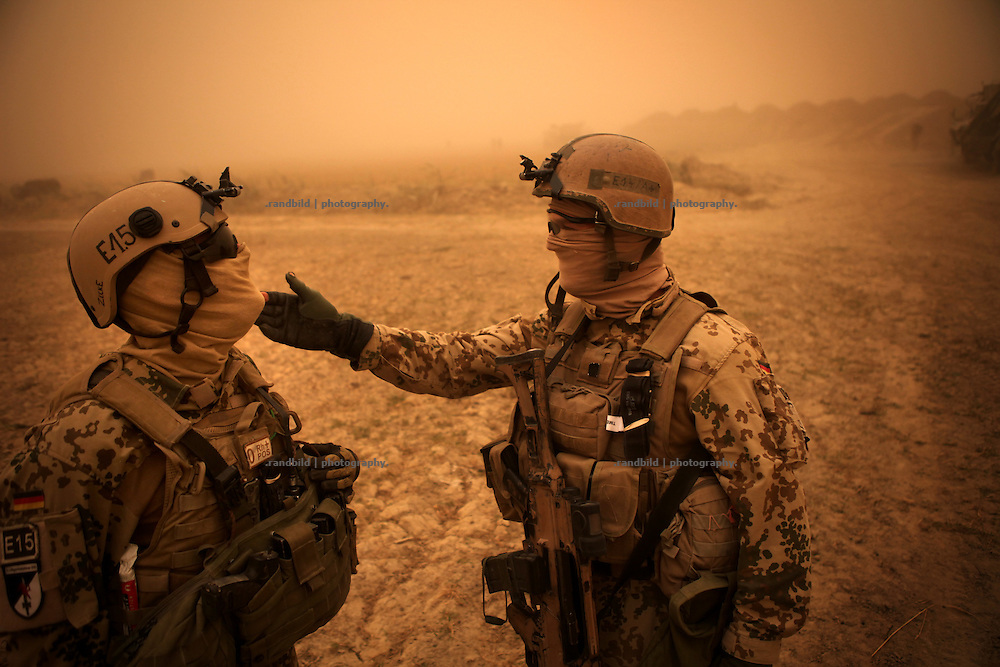 Two soldiers kidding. After two armored trucks of the ECHO platoon stuck in moody fields near Rahmat Bay, soldiers cover the area during a strong sandstorm while their comrades try to rescue the vehicles. In late October 2011 Kunduz based 3.Task Force started a several days operation in and around Nawabad (District Chahar Darah), west of Kunduz, northern Afghanistan. During the Operation Orpheus about 100 german infantery soldiers rolled out for patrols through the town and surrounding areas, which were expected as a retreat zone of insurgents.