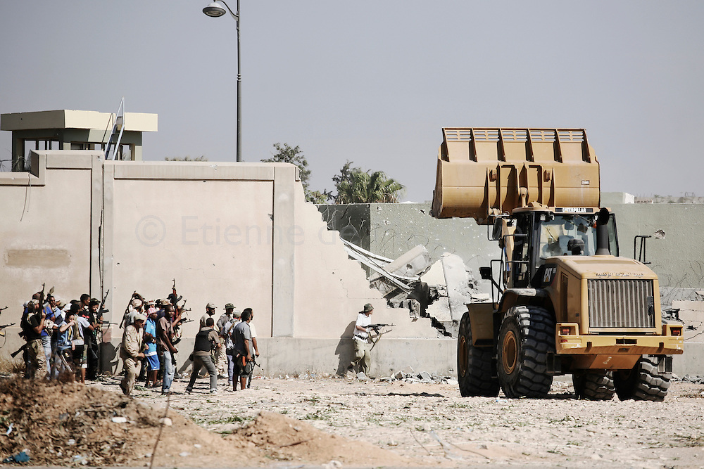 Rebel Libyans attacks Gaddafi's headquarters in Bab Al Azizyia compound in Tripoli.  A Caterpillar breaks open a breach in the outer wall of the compound. 23 August 2011.