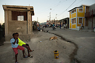 Two brothers sit by the side of the road at a spot where a 2010 quake house collapse killed at least one woman, in the Fort National neighborhood of Port-au-Prince, Haiti, January 3, 2015.  Across the street are new homes built by an UNOPS program.