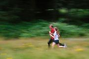 Young adult couple jogging on Pre's Trail, Alton Baker Park, Eugene, Oregon.