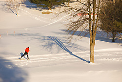 A man cross-country skiing (track skiing) on a groomed trail next to the frozen Ottauquechee River in Quechee, Vermont. Model Release.